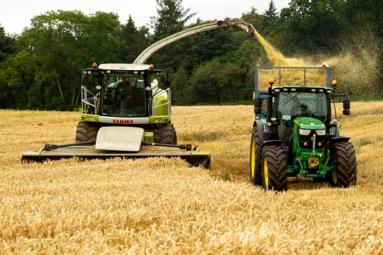 A tractor and combine harvester in a field