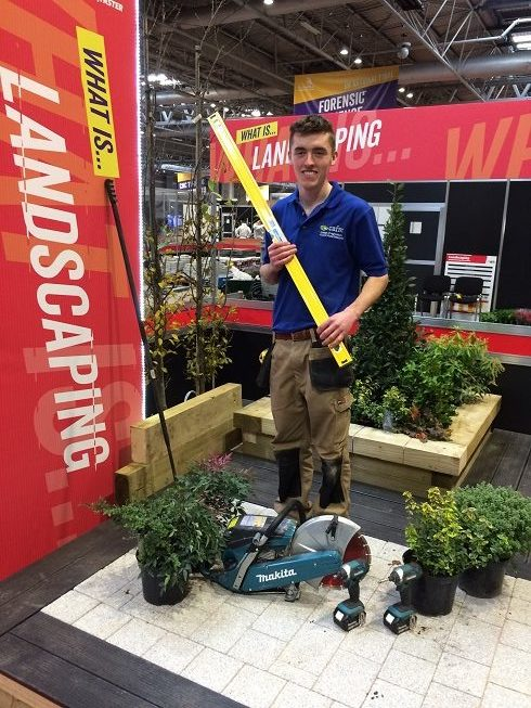 Man surrounded by plants while holding a spirit level