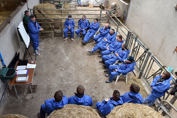 Group of people at a training event inside a barn.