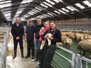 A group of people in a sheep pen. two are holding lambs