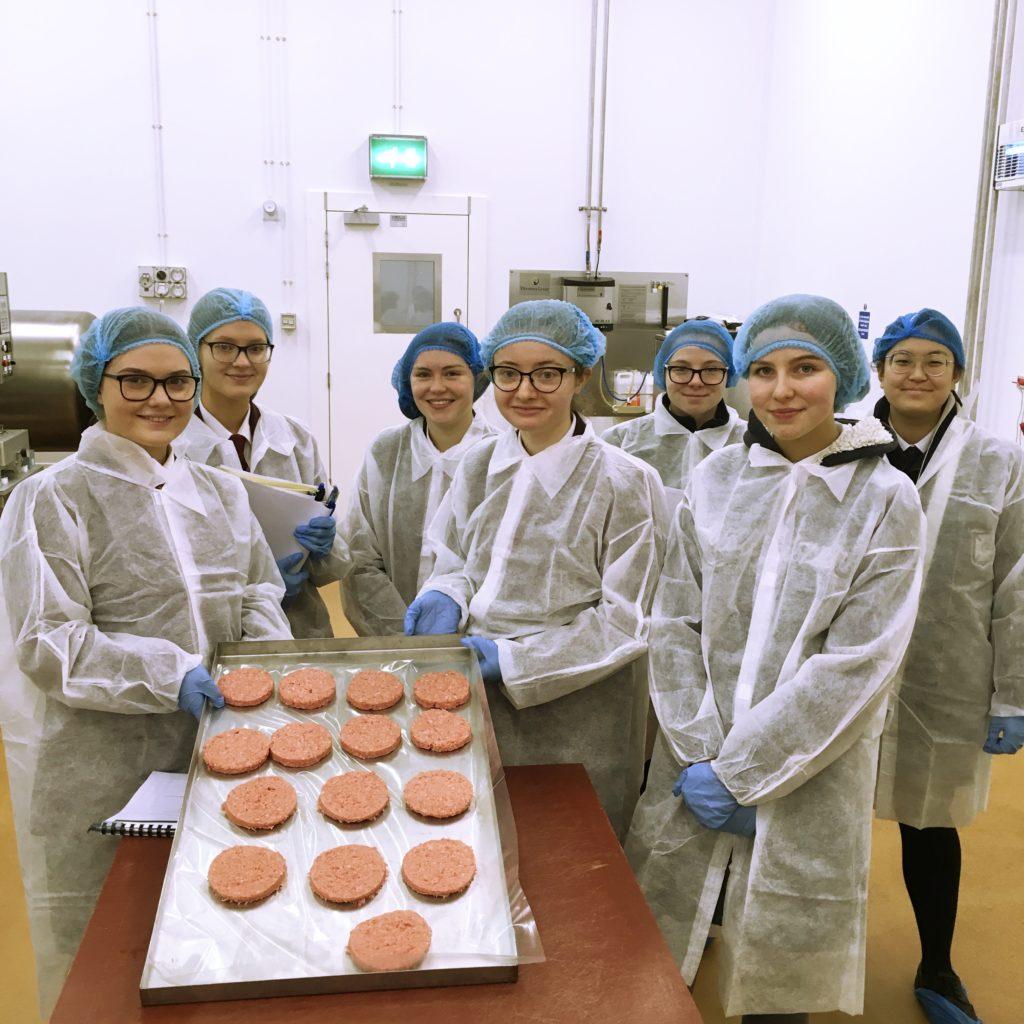 school-pupils-in-lab-coats-making-burgers