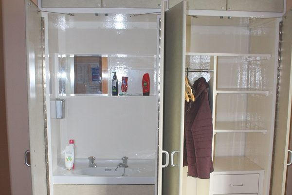 Wardrobe and cupboard with a sink inside it