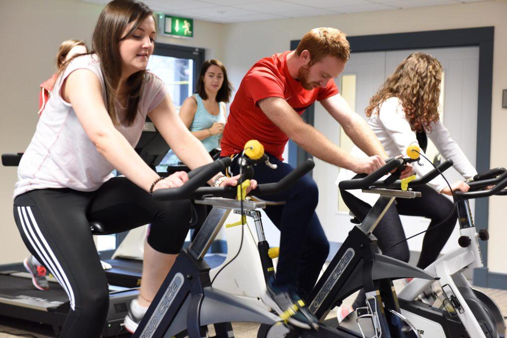 Three people riding exercise bikes