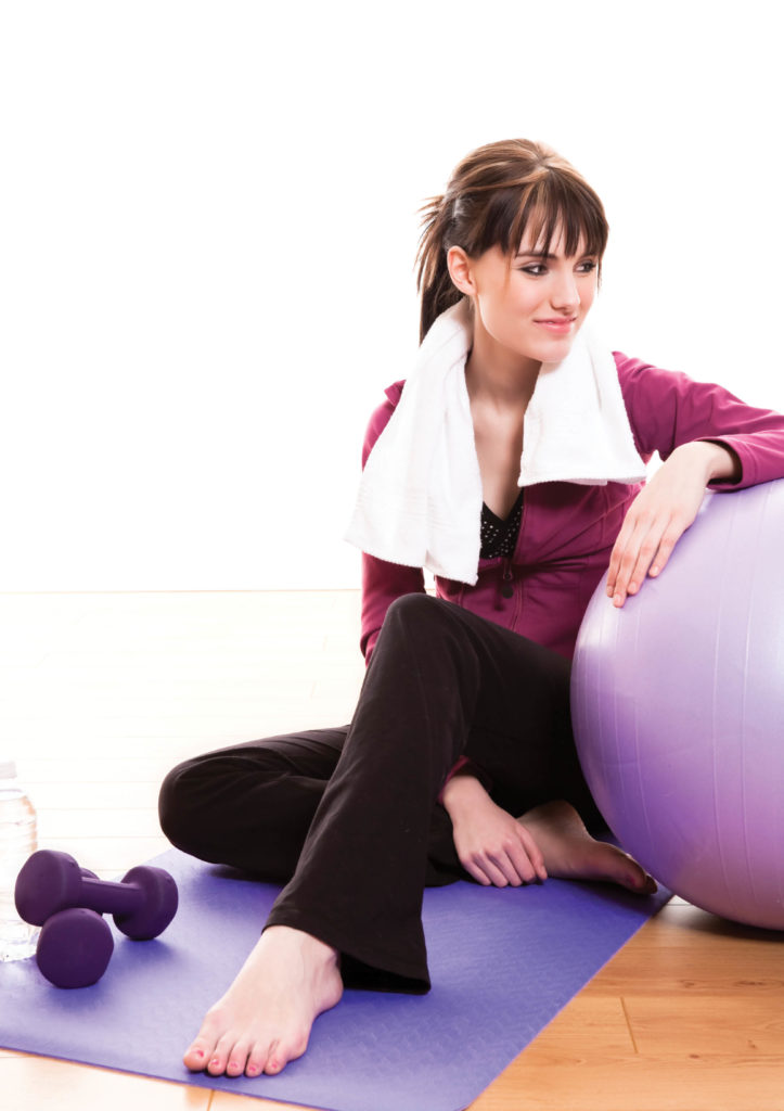 Woman beside exercise ball getting ready for a workout